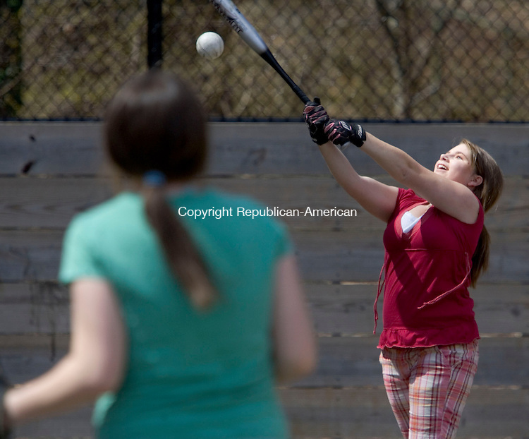 WATERBURY, CT- 14 APRIL 2008- 041408JT17-<br /> Brittany Rizk, 14, of Watertown, takes a swing at a pitch made by her cousin Lyndsey Rizk, also 14, in the foreground, on Monday at Bunker Hill Park in Waterbury.<br /> Josalee Thrift / Republican-American
