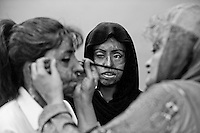 Urooj Akbar,26 (L) having make-up applied to her face by Depilex founder Massarat Misbah, while Saira Liaqat looks on before the start of their shift...Urooj had acid thrown at  her face 5 years ago by her husband after giving birth to a daughter...Stigmatised by her family, She now lives at a hostel.