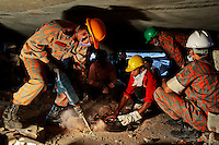 A Bangladeshi rescuer works to break through metal and concrete with a drill at the site of a building that collapsed Wednesday in Savar, near Dhaka, Bangladesh, Friday, April 26, 2013.
