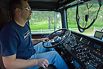 Dump truck owner operator driving in cab with windshield, dash and radio mics