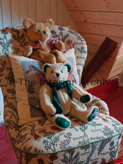 Two teddy bears sit on an armchair upholstered in an English fabric woven with images of herbs