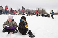 Youngsters Kaylila Johnston (L) and Joshua Nikolai watch as Sylvia Willis arrives at the Nikolai checkpoint during Iditarod 2008