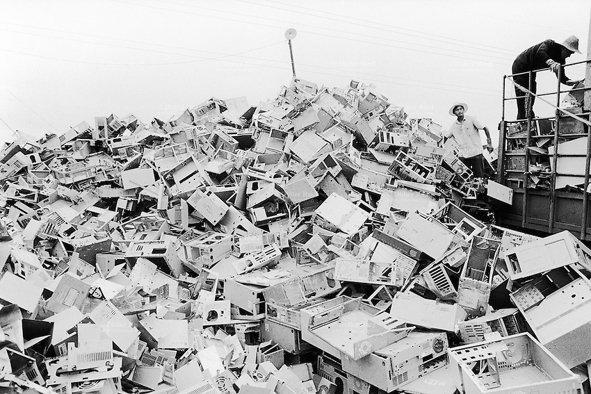 China. Province of Guangdong. The village of Beilin is part of the town of Guiyu. Computers heap. Workers load a tuck with metals chassis, taken down from old computers and stocked on a pile. The various parts will be recycled for its metal. © 2004 Didier Ruef