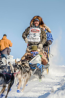 Cody Strathe and team run past spectators and down the Cordova Street hill with an Iditarider in the basket and a handler during the Anchorage, Alaska ceremonial start on Saturday March 4th during the 2017 Iditarod race. Photo ©2017 by Daniel Lent/SchultzPhoto.com