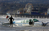Two people died Monday when their Beechcraft airplane en route from Santa Monica to San Diego crashed in the ocean near the Santa Monica Pier, Monday, March 13, 2006. Rescue personal and Los Angeles Fire dept. pull the plane from the water Monday afternoon, Santa Monica pier in the background.