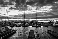 Empty boatslips and idle sailboats, their masts pointing heavenward toward a skyfull of storm cloud remnants.  Sunset at the San Leandro Marina in black and white.