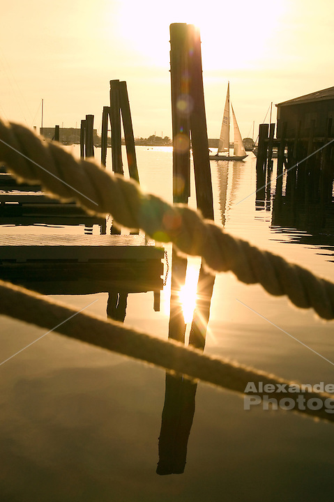 USA, Newport, RI - A sheilds class racing sloop sails in the distance past the dock lines of a yacht on Bannister's wharf in the late afternoon sun.