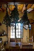 Herbs hanging to dry in a rustic style kitchen and dining area at a buddhist center in Santa Fe, NM