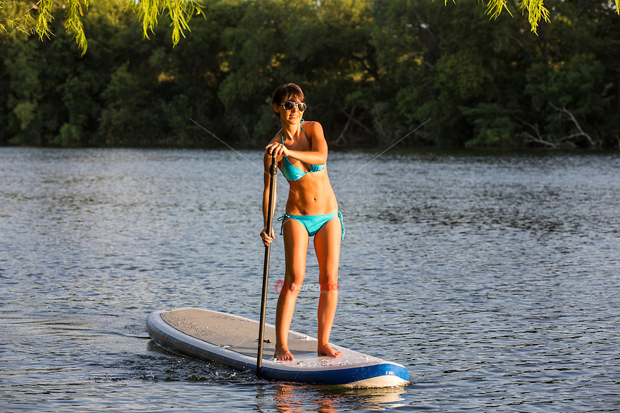 An attractive tan young woman in bikini paddles a stand up paddle board SUP on the prestine blue waters of Lady Bird Lake in Austin, Texas.