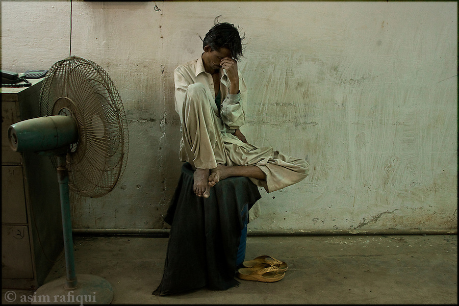 at a garment factory in karachi, a worker grabs a quick rest during a 12-hour work shift