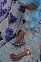 Muslim women communicating with her cellphone,Manila Philippines