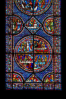 Medieval stained glass Window of the Gothic Cathedral of Chartres, France - dedicated to the Life of St Mary Magdalen. Bottom central panel - bottom left - Mary washing Christ's feet in the house of Simon the Pharisee, bottom right - Death of Lazarus, top left - Their neighbours try to console Mary and Martha, top right - Funeral of Lazarus. Diamond panel above and side panels either side - Christ raising Lazarus. A UNESCO World Heritage Site..
