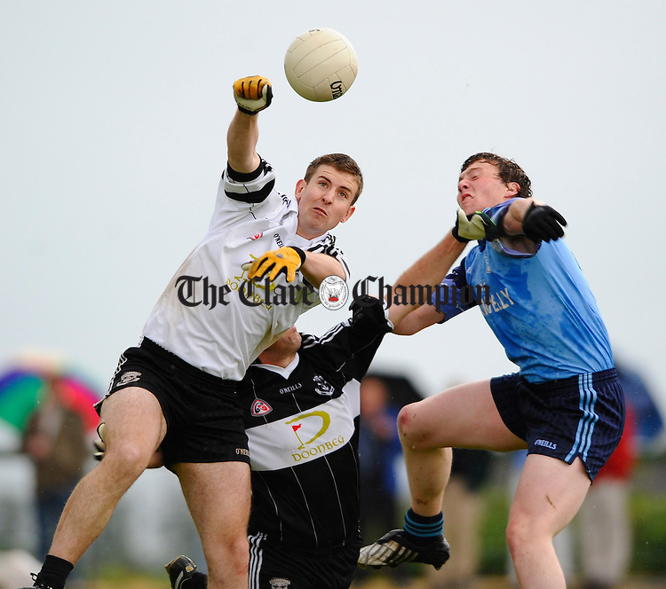 Doonbeg goalie Brian Dillon fists the ball away from Cooraclare's Padraig Looney during their Cusack Cup sem-final at Kilmihil. Photograph by John Kelly.