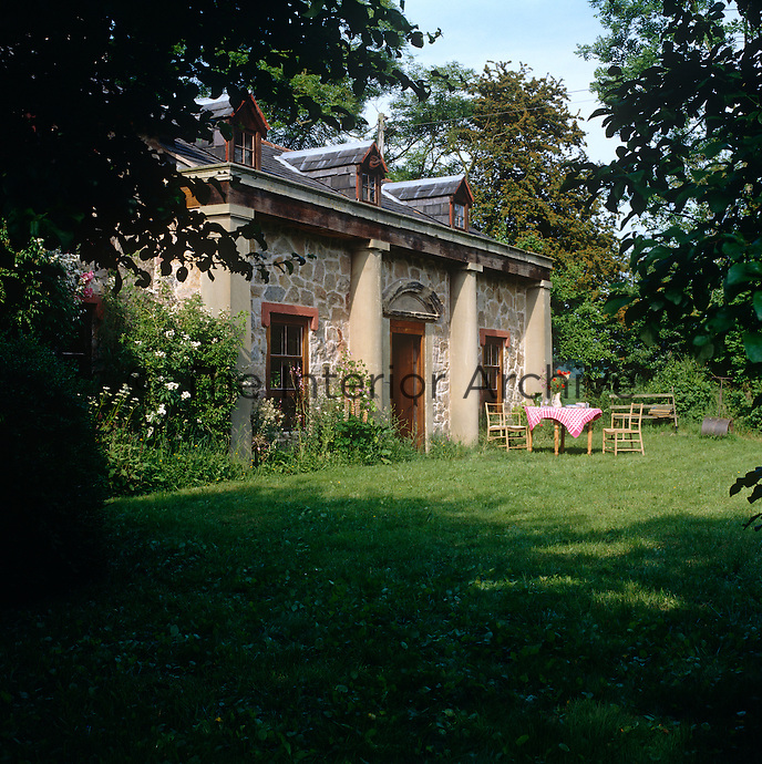 A simple table and chairs have been placed in the informal back garden of this charming house in the country