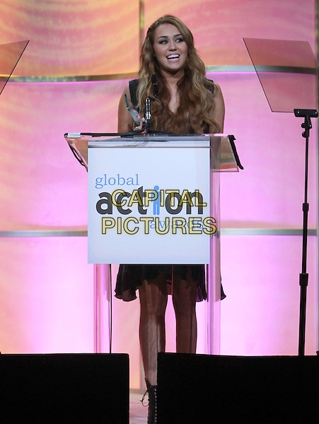 MILEY CYRUS .First Annual Global Action Forum Gala - Inside Held At The Beverly Hilton Hotel, Beverly Hills, California , USA, .18th Febuary 2011..full length black dress podium on stage microphone speaking .CAP/ADM/KB.©Kevan Brooks/AdMedia/Capital Pictures.