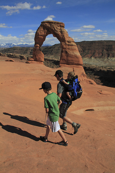 Father and children at Delicate Arch in Arches National Park, Moab, Utah, USA. .  John offers private photo tours in Arches National Park and throughout Utah and Colorado. Year-round.