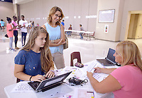 NWA Democrat-Gazette/BEN GOFF &bull; @NWABENGOFF<br /> Melanie Taylor (right), testing coordinator at Bentonville High School, helps junior Maggie Clark, 16, sign up for parking with mother Lisa Clark on Thursday Aug. 6, 2015 during student schedule pickup at Bentonville High School. Bentonville High and other traditional-schedule schools in the district resume classes on Tuesday, Aug. 18.