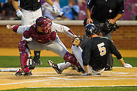Evan Stephens #5 of the Wake Forest Demon Deacons slides across home plate ahead of the tag by Florida State Seminoles catcher Stephen McGee #9 in the bottom of the 5th inning at Wake Forest Baseball Park on March 23, 2012 in Winston-Salem, North Carolina.  (Brian Westerholt/Four Seam Images)