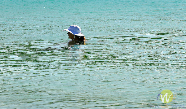 Saltpond bay and beach, St. John, USVI, Caribbean. Islands National Park. Woman in water with hat.
