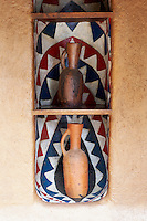 Pottery jugs are displayed on shelves in a recess in the living area
