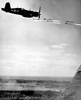 Corsair fighter looses its load of rocket projectiles on a run against a Jap stronghold on Okinawa.  In the lower background is the smoke of battle as Marine units move in to follow up with a Sunday punch.  Ca.  June 1945.  Lt. David D. Duncan.  (Marine Corps)<br /> Exact Date Shot Unknown<br /> NARA FILE #:  127-GR-97-126420<br /> WAR & CONFLICT BOOK #:  1224
