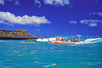 Outrigger canoe with group of people riding a wave in Waikiki; Diamond head in backround