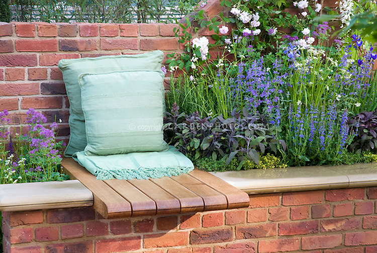 Garden seating next to roses herbs flowers built into brick wall