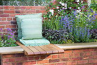 Garden bench and pillows with raised flower border with herbs Salvia officinalis, brick wall interplanting flowers and herbs