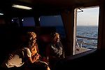 Long Beach Island, NJ - June 29, 2013 :  On Miss Barnegat Light sunset cruise, Miranda Law, 16, Linda Bensen and Cathy Cepican from Oak Lawn, IL, watches the sun set over Barnegat Lighthouse, built in 1857, on the northern tip of Long Beach Island, NJ on June 29, 2013. The women were part of a Lutheran church mission group visiting Long Beach Island to help with the post Hurricane Sandy clean up. People are returning to the beaches for the summer after recovery efforts post Superstorm Sandy.