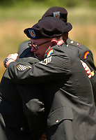 ARNYTOWN, NJ - JUNE 12:  Member of New Jersey National Guard Sgt. Frank Carvill's unit embrace after the commital service for Sgt. Carvill at Brigadier General William C. Doyle Veterans Memorial Cemetary June 12, 2004 in Arnytown, New Jersey. Carvill, 51, of Carlstadt, New Jersey, and three other New Jersey National Guardsmen were killed during a two day period one week ago in Iraq. (Photo by William Thomas Cain/Getty Images)
