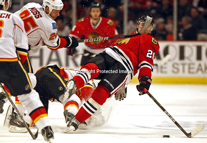 """Chicago Blackhawks' Jack Skille gets Calgary Flames' David Moss' stick in the face drawing a 4-minute penalty in 1st period of Hawks' 4-2 win during NHL hockey at United Center in Chicago, IL on Sunday, December 5, 2010..""""Jack Splat""""."""