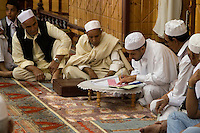 "Tripoli, Libya.  Muslim Wedding Celebrations.  Preparing Marriage Contract for Signing; Sheikh (""Ma'doun"") Officiates, while male family and friends witness."