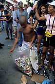 Salvador, Brazil. Carnival; boy collecting empty drink cans for recycling amongst the revellers and rubbish. Bahia State.