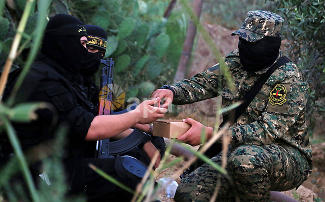 Palestinian militants from the Al-Quds Brigades, the armed wing of the Islamic Jihad movement break their fast as they guard the border between the Gaza Strip and Israel on the Muslim holy fasting month of Ramadan on June 17, 2017. Ramadan is sacred to Muslims because it is during that month that tradition says the Koran was revealed to the Prophet Mohammed. The fast is one of the five main religious obligations under Islam. More than 1.5 billion Muslims around the world will mark the month, during which believers abstain from eating, drinking, smoking and having sex from dawn until sunset. Photo by Dawod Abo Elkass