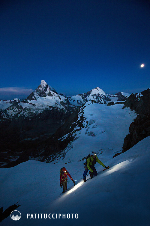 Two alpine climbers at sunrise on the Obergabelhorn's Arbengrat, above Zermatt, Switzerland with the Matterhorn in the background