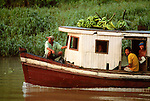 Local men traveling with bunches of green bananas in a riverboat on the Amazon River in Peru. The Amazon is the world's largest river, and serves as the main route for transport throughout the remote forested regions of the Amazon basin. [No Model Release]