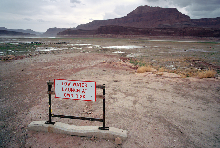 A warning sign sits high and dry at the foot of a boat ramp at Hite Marina in southern Utah as the Colorado River cuts a new channel through lakebed sediments more than a quarter mile away on the opposite canyon wall. As the river flows through a new delta over land once covered by the Lake Powell reservoir, dried silt slumps toward the river, developing cracks up to five feet deep as layers of the sediment are washed out by the river below. The canyons have filled with silt and sediments when the waters of the reservoir rise in the canyon. Now with low water the river is eroding those lake sediments and washing them into Lake Powell, geologist Dr. John C. Dohrenwend asserts. He is studying the creation of the Colorado River's delta at Lake Powell and the erosion and motion of sediments into the lake. Dohrenwend, a retired U.S. Geological Survey geologist, fears the sediment flow may fill the reservoir more quickly than the builders of the Glen Canyon Dam thought. This would reduce the storage capacity of the reservoir and possibly compromise the dam itself. At rear is the Hite Crossing bridge. (Kevin Moloney for the New York Times)
