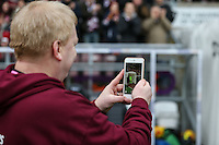 A supporter videos the players entering the pitch during the Sky Bet League 2 match between Northampton Town and Morecambe at Sixfields Stadium, Northampton, England on 23 January 2016. Photo by David Horn / PRiME Media Images.
