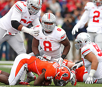 Ohio State Buckeyes defensive lineman Noah Spence (8) gets up after tackling Illinois Fighting Illini running back Josh Ferguson (6) during the NCAA football game at Illinois on Saturday, November 16, 2013. At left is teammate Ohio State Buckeyes defensive lineman Michael Bennett (63). (Columbus Dispatch photo by Barbara J. Perenic)