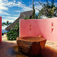 A monolithic stone fountain, inspired by old fonts, is sheltered by a pink wall