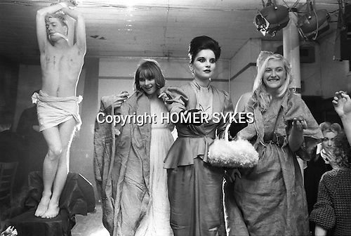 Blitz Kids New Romantics at The Blitz Club Covent Garden, London, England 1980. At the Easter Pageant,  Princess Julia (centre ) handing out Cadburys Creme chocolate Easter eggs to the crowd. They had just performed the song, Death Where is Thy Sting?  [L-R] Iain R Webb [fashion author, editor journalist],  Jennifer Binnie,  and sister Christine &quot;Miss Binnie&quot;<br /> <br /> &quot;Instead of &lsquo;RIP&rsquo; Princess Julia scrawled &lsquo;HIP&rsquo; on my chest in lipstick, &quot; writes Iain R Webb.