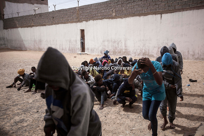 Illegal female migrants queue in the prison yard as they are loaded onto buses to be transferred to another detention centre, after having been sold by the militia group ruling the Surman detention camp in the west of Libya.