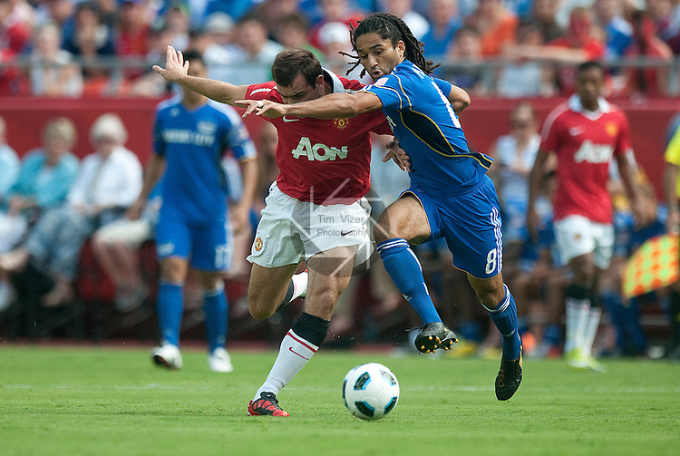 """July 25, 2010          Manchester United defender Ritchie De Laet (30, left) battles for control of the ball with Kansas City Wizards midfielder Stephane Auvray (8).  The Kansas City Wizards of Major League Soccer defeated Manchester United of the English Premier League 2-1 in an international friendly game on Sunday July 25, 2010 at Arrowhead Stadium in Kansas City, Missouri.  The game is the third of four stops for Manchester United on their """"Tour 2010""""."""