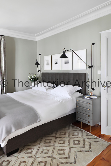 A stylishly monochrome design scheme of crisp white bedding teamed with a variety of greys throughout the room, whilst black wall lights and a set of black and white photographs are mounted on the wall around the bed