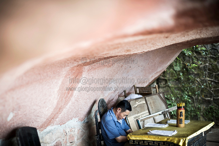 """A Chinese calligraphy master takes a rest in the Bamboo Sea National Park in Yibin, Sichuan, China, August 07, 2014. <br /> <br /> This image is part of the series """"24/7"""", an ironic view on restless and fast-growing Chinese economy described through street vendors and workers sleeping during their commercial daily activity. <br /> <br /> © Giorgio Perottino"""