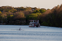 Rower trains on Lake Austin as a Cruise Boat passes by on Town Lake, Austin, Texas, USA
