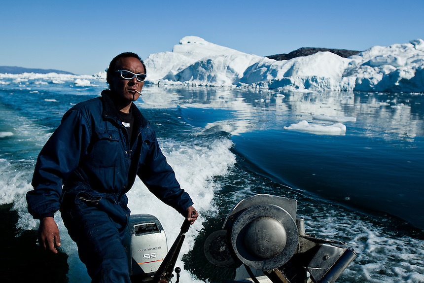 A Greenlandic Inuit fisherman navigates his small fibreglass boat through icebergs off the coast of West Greenland, August 2011. Photo: Ed Giles.