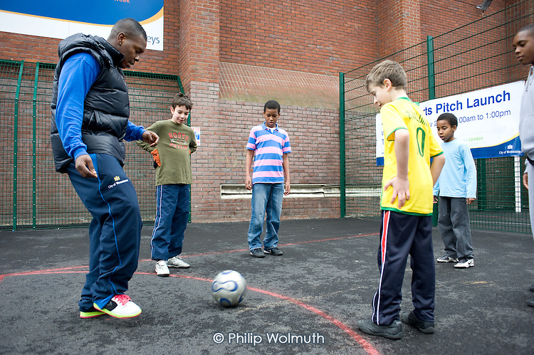 A coach demonstrates ball skills to children from a Westminster Sports programme play football on a new outdoor pitch at Jubilee Sports Centre