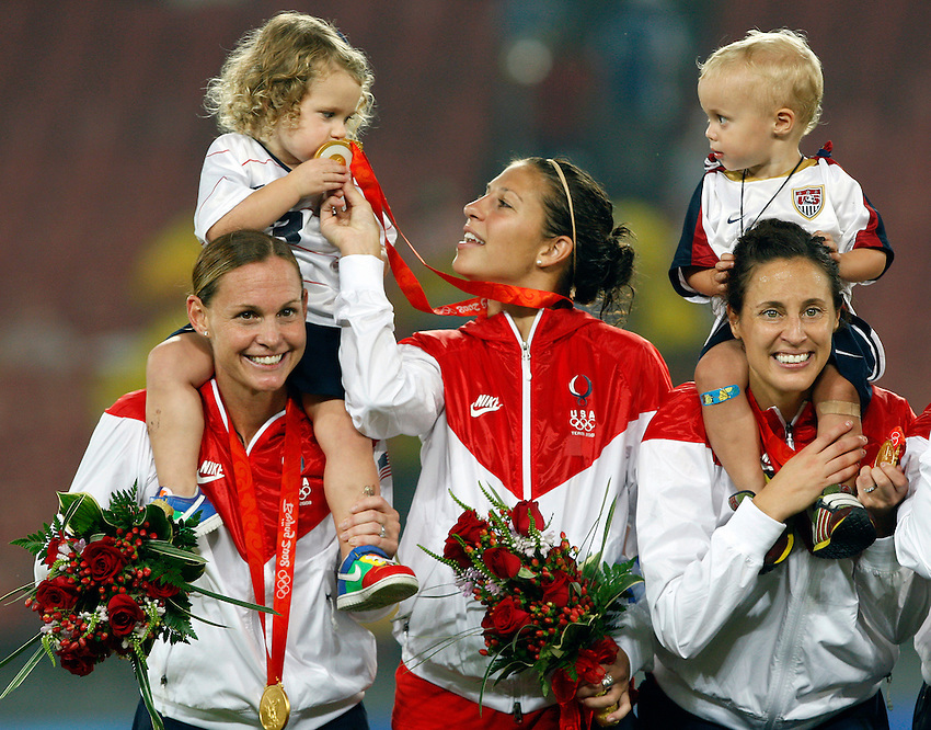 BEIJING -- Kylie Rampone, 3, on her mom Christie Rampone's shoulders, kisses the gold medal of Carli Lloyd (center) as Keegan Markgraf, 2, with his mom Kate Markgraf  look on atop the medal platform as the United States celebrates its win over Brazil in the gold medal women's soccer game at Workers' Stadium at of the Beijing 2008 Olympic Games. The Rampone family is from Manasquan, N.J. and Lloyd, who scored the game's only goal is from Delran, N.J.  (8/21/08)  ANDREW MILLS/THE STAR-LEDGER..