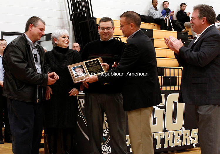 Waterbury, CT- 23 December 2013-122313CM05- Left to right, David Ierardi, Donna Ierardi and Richard Ierardi accept a plaque from Dick Kulmann, a long time friend of Ierardi and Marty Sparano, former athletic director inside the newly named Dick Ierardi Gymnasium inside Kaynor Tech High School in Waterbury Monday night.  A dedication ceremony was held honoring the former athletic director at the school. Ierardi coached their basketball team for 17 years.  Ierardi also served as the school's physical education teacher and as an assistant director.    Christopher Massa Republican-American
